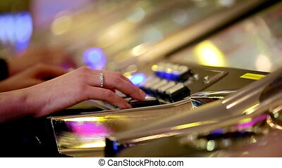 casino: man and woman playing slot machines. close-up