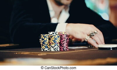 Casino: Man playing poker, excited, turns casino tokens in hand. Close up,