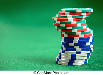 Casino poker chips on green table background