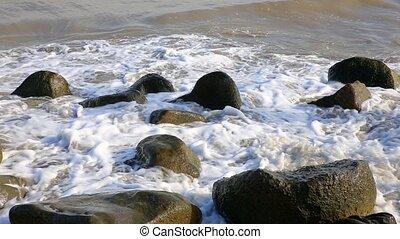 Caspian Sea, Iran, sea waves break against stones on the shore.