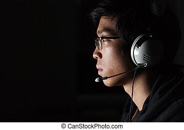 casque à écouteurs, salle, jeune, sombre, utilisation, sérieux, homme