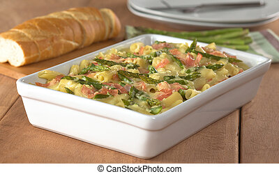 Casserole of green asparagus, ham and macaroni with baguette slices and plates in the back (Selective Focus, Focus in the middle of the dish)