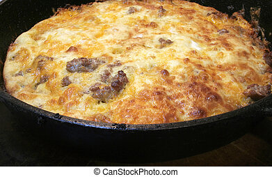 Pork sausage, biscuit mix, and chedder cheese casserole in a black cast iron skillet.