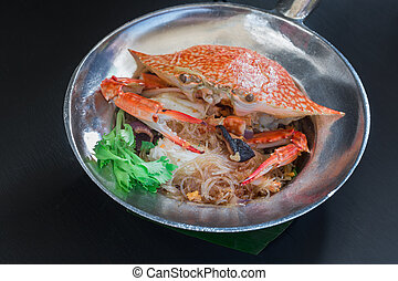 Casseroled crab with glass noodles on black background