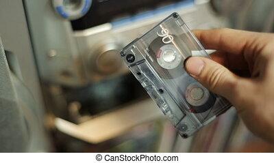 Cassette tape into record player - Man puts cassette tape...