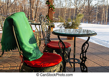 Cast iron chairs and tables with pillows and a blanket on restaurant terrace. Winter landscape of frosty trees, white snow and blue sky. Tranquil winter nature in sunlight in park