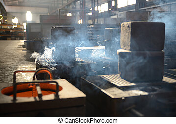 cast iron cools - Smoke arises from hot moulds of cast iron...