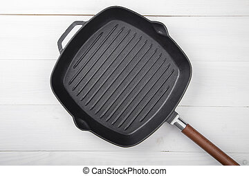 Cast-iron grill pan on a wooden surface. View from above.