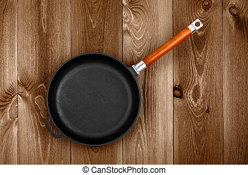 Cast Iron Skillet - Empty cast iron skillet on a wooden ...