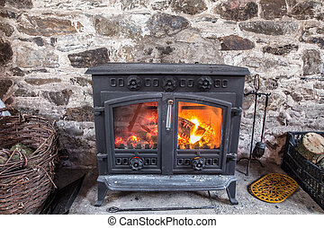Cast iron stove burning wood logs against a robust stone wall