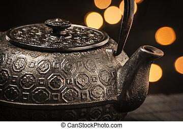 Cast iron teapot - Closeup of a black, cast-iron teapot on a...