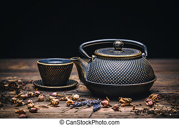 Cast iron teapot with small cup over wooden background