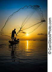 Casting a silhouette at sunset on the lake, Thailand.