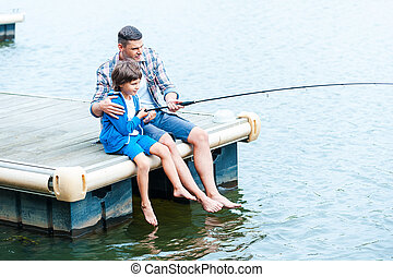 Casting off together. Top view of father and son fishing together on quayside