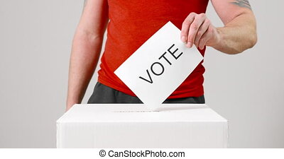Casting vote into the ballot box by young casual and ...