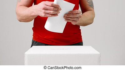 Casting vote into the ballot box - Young casual and tattooed...