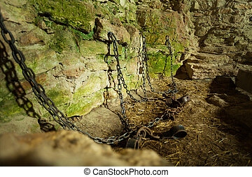Castle dungeon prison with chains chain and moss on stone walls