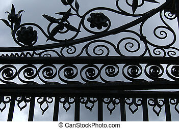 Close-up of castle gates silhouetted against a stormy sky