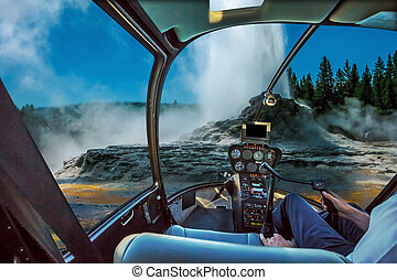 Helicopter cockpit flight over Castle Geyser with hot water and steam pools of thermophilic bacteria and cone geyser in Upper Geyser Basin of Yellowstone National Park, Wyoming, United States.