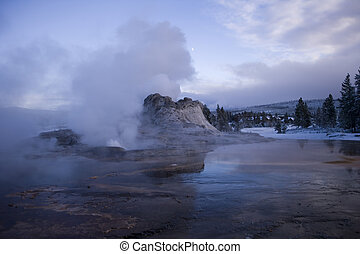 Evening shot of Castle Geyser with the moon behind the stream vent