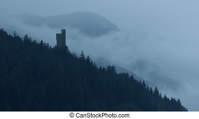 Castle In Misty Mountains - Castle on mountainside in the...