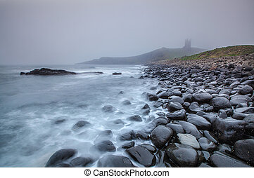 Castle in the storm, Dunstanburgh, England.