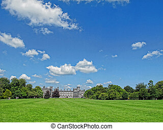 Castle on a meadow in Ireland with blue sky and clouds