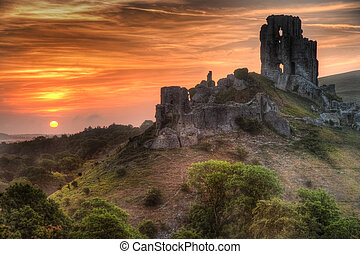 Landscape with castle ruins on hill and vibrant beautiful sunrise in distance