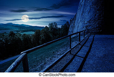 castle wall and railing on a hill at night in full moon...