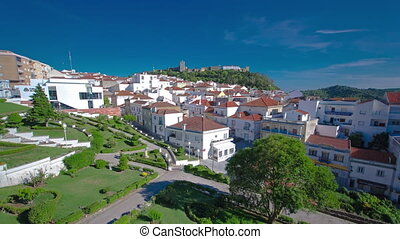 Castle with houses with red roof near the city Sesimbra,...