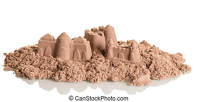 Castles in the sand close up isolated on white.