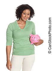 Casual African American young female standing with a pink piggy bank against white background