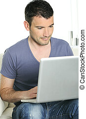 casual attractive man is surfing on web with his computer