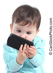 Casual baby watching attentive a mobile phone isolated on a...