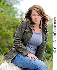 Beautiful girl sitting outdoors in casual clothing.