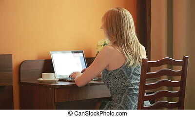 beautiful woman working on a laptop sitting on the table in the house.