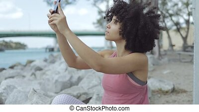 Casual black girl taking selfie on riverside - Young curly...