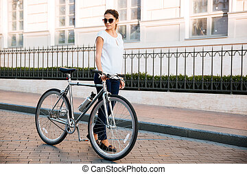 Casual brunette woman cyclist standing near a bike