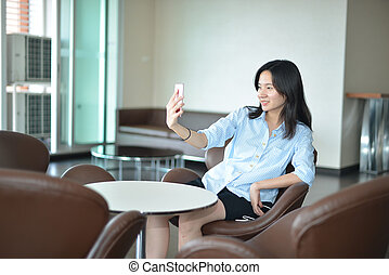 Casual Business Asian Woman taking a selfie with smartphone