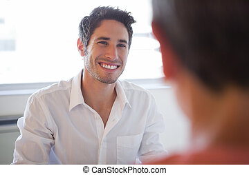 Casual business people talking at desk and smiling
