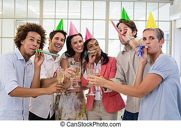 Casual business team celebrating with champagne and party horns