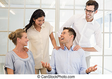 Casual business team congratulating colleague in the office