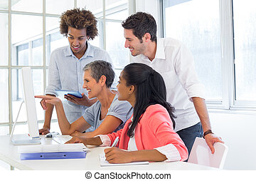 Casual business team having a meeting with computer