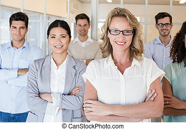 Casual business team smiling at camera with arms crossed in...