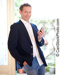 Casual businessman smiling with mobile phone
