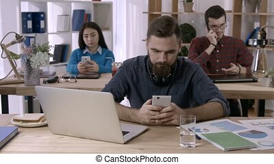 Casual businessman texting on smartphone in office