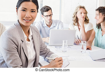 Casual businesswoman smiling at camera during meeting in the...