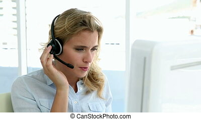 Casual call centre worker working at her desk in casual...