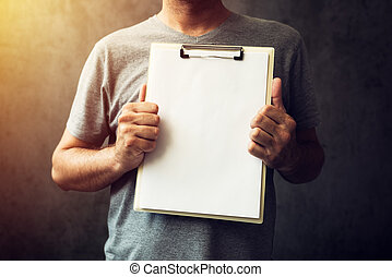 Casual caucasian adult man holding blank notepad paper