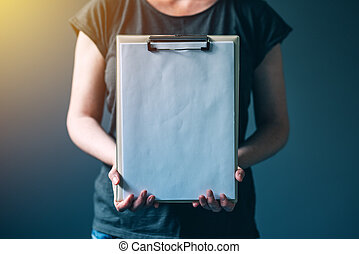 Casual caucasian adult woman holding blank notepad paper